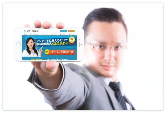 モニターサイトの画面を見せる男性